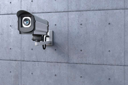 security camera watching to the left on concrete wall photo