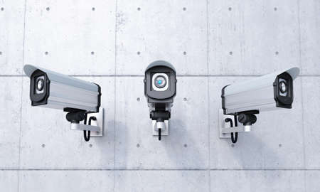 Three Security cameras frontal view on concrete wall Imagens