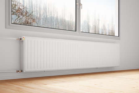 and heating: Central heating attachted to wall with closed windows Stock Photo