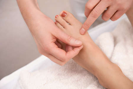 anesthetize: Acupuncture treatment on foot with red toenail Stock Photo