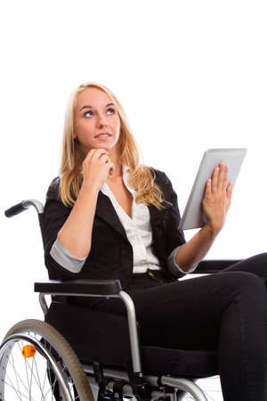 paraplegic: Blond girl sitting in a wheel chair with tablet PC Stock Photo