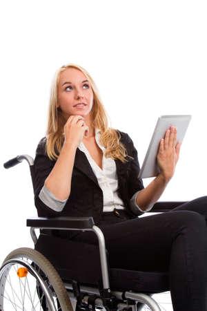 paraplegico: Chica rubia que se sienta en una silla de ruedas con Tablet PC Foto de archivo