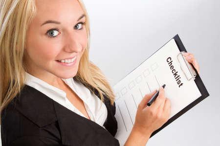 control de calidad: Mujer joven con la lista de verificaci�n sobre el hombro de disparo aislado en blanco Foto de archivo