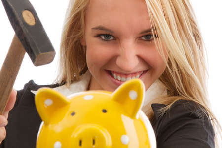 Young woman smashing piggy bank isolated on white photo