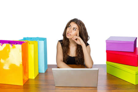 spendthrift: Woman sitting on laptop shopping with boxes und bags