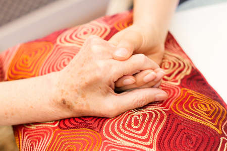 caring for: Young hands caring for old hands on a red cushion