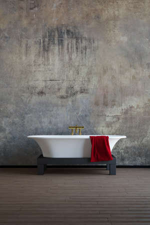 Old bath tube with red towel and wooden floor