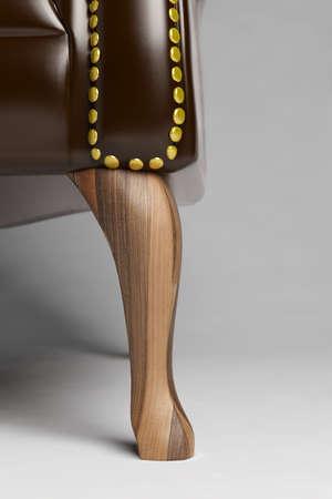 Nahaufnahme des hölzernen Fuß von einem Stuhl aus Leder Standard-Bild - 31237989