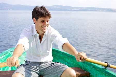 Smiling male model woring a green boat on a lake photo