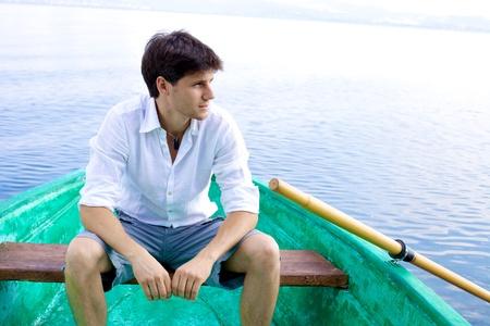 Feliz el hombre fresco joven sentado en un barco de madera en un lago sonriente Foto de archivo