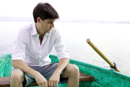 Young man sitting on a boat in a lake thinking expressing sadness Stock Photo - 15250645