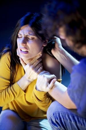 violencia intrafamiliar: hombre estrangulando y sosteniendo el pelo de la mujer en el dolor la violencia dom�stica