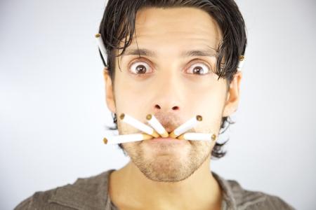 Man met slechte gewoonte van het roken gek geworden met vele sigaretten in de mond