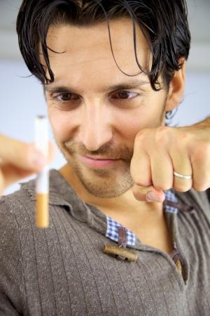 Modelo masculino sonriente con cigarrillo en mano parada de fumar Foto de archivo