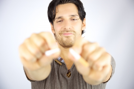 Handsome man smiling breaking cigarette in two pieces stop smoking no cancer photo