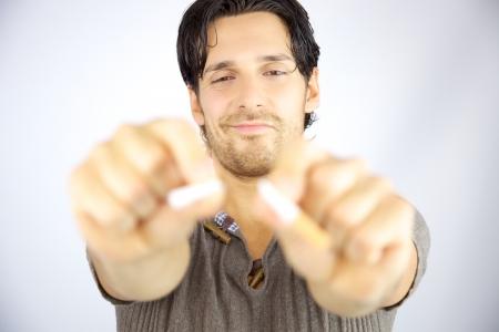 Hombre guapo sonriendo cigarrillo romper en dos pedazos dejar de fumar sin cáncer Foto de archivo