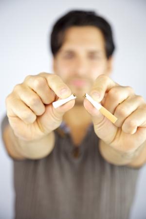 Cigarrillos que se rompió en dos pedazos por la adicción hombre parada para dejar de fumar Foto de archivo