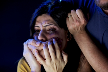 Strong man holding face of beautiful desperate woman crying