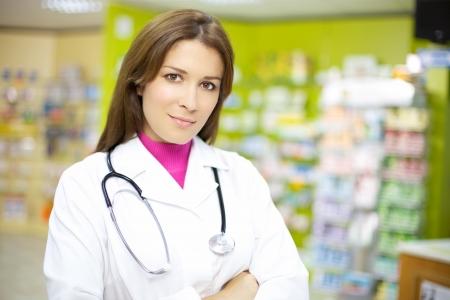 Aantrekkelijke vrouwelijke arts werken in de farmacie gelukkig