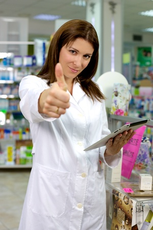 experienced: Pharmacist in pharmacy with tablet and thumb up Stock Photo