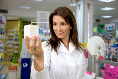 Good looking female pharmacist working in pharmacy happy
