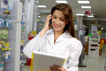Farmacéutico hermoso que habla en el teléfono feliz Foto de archivo