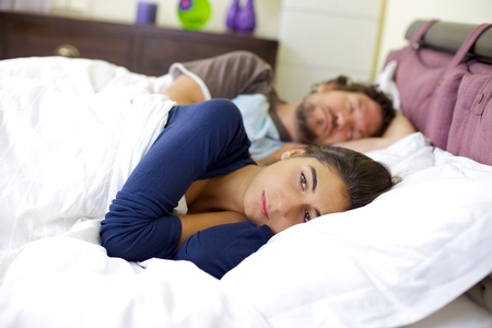 Depressed woman in bed while husband is sleeping not caring about her