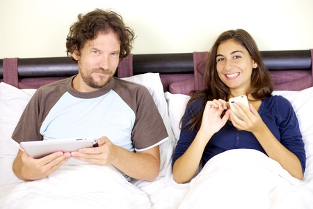 Happy husband and wife in bed with electronic tablet and phone photo