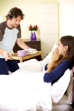 Happy woman getting continental breakfast in bed from smiling husband photo