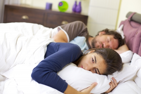 sad young woman laying in bed crying after fight with husband photo