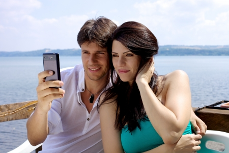 Gorgeous couple taking picture with cell phone during vacation happy photo