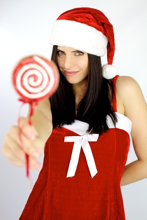 Happy gorgeous female santa claus holding lollipop  for christmas photo