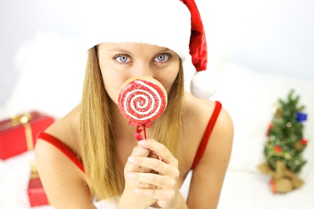 Happy santa claus woman with blue eyes and lollipop in hand photo