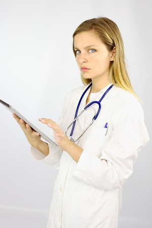 Gorgeous blond doctor working with ipad tablet serious photo