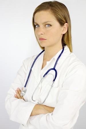 Hermosa mujer médico mirando serio con el estetoscopio aislado