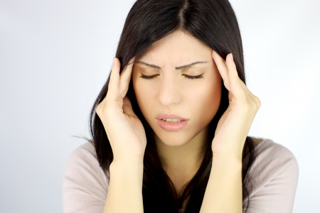 headache: Depressed young woman with terrible headache touching head with hands