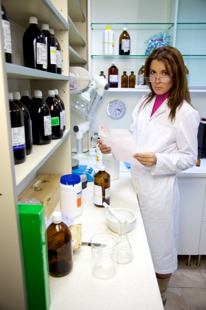 pharmaceutic: Serious female pharmacist working in laboratory with prescription medicine and chemicals