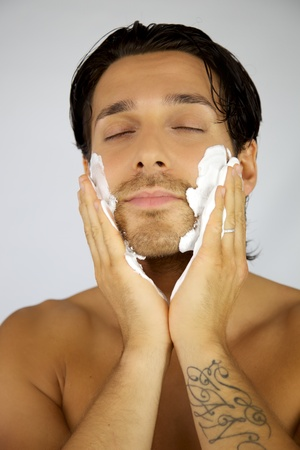 Handsome man putting much shaving cream on his face photo
