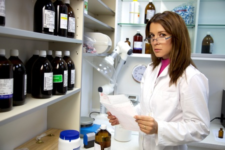 pharmacy technician: Good looking pharmacist working in laboratory serious Stock Photo