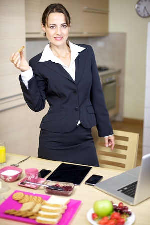 businesswoman suit: Gorgeous female model businesswoman in suit having breakfast at home in the morning