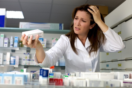 knowing: Angry woman pharmacist not knowing what to do with medicine