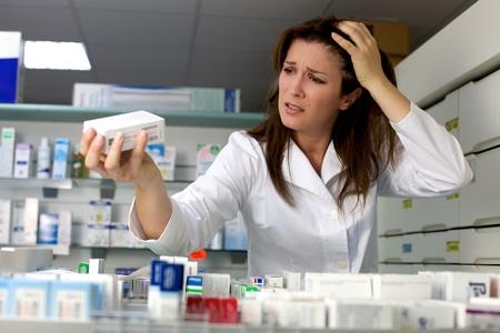 Mujer enojada farmacéutico no saber qué hacer con la medicina Foto de archivo