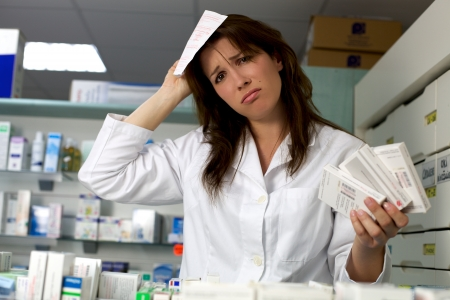 Ongelukkige vrouw apotheker wanhopig in de farmacie Stockfoto