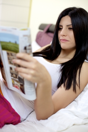 Woman having fun reading magazine in bed relaxed photo