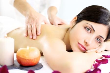 Unas manos fuertes que hacen masaje en la espalda de la bella modelo femenino en el balneario blanco relajarse durante las vacaciones