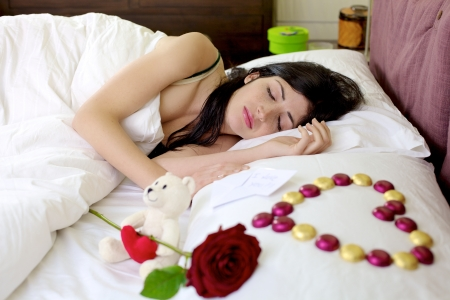 Gorgeous female model sleeping relaxed with san valentines gift waiting for her, rose, chocolate heart, love message photo