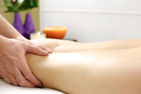 get tired: Hands of therapist doing massage to tired legs to get the stress out