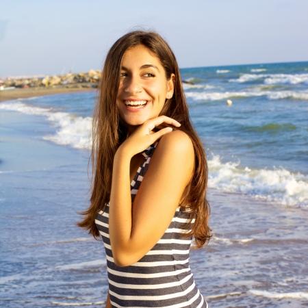 Mujer feliz sonriente conseguir curtida frente al mar