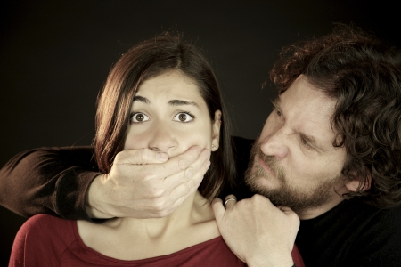 hostage: Terrified young woman held hostage by bad scary man