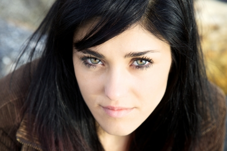serious face: Gorgeous young woman looking with big green eyes